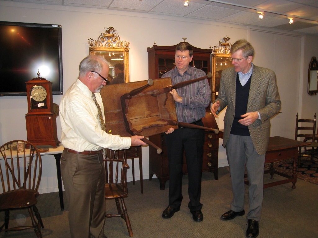 From left, Steve Fletcher, Gary Sullivan, and Jobe examine a table at a work­shop at Skinner Auctioneers.