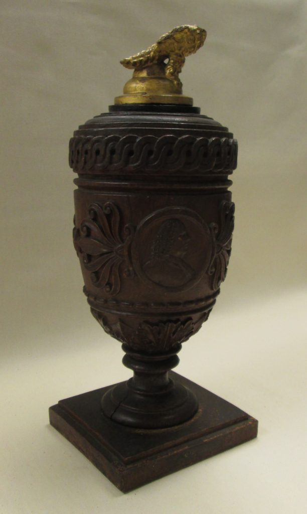 "Maker unknown [George Magraph, attributed], ""Urn made from the Treaty Elm,"" 1813, wood, glass, 15 1/2 x 6 x 6 in., HSP.19871.1 Courtesy of the Philadelphia History Museum at the Atwater Kent, The Historical Society of Pennsylvania Collection."